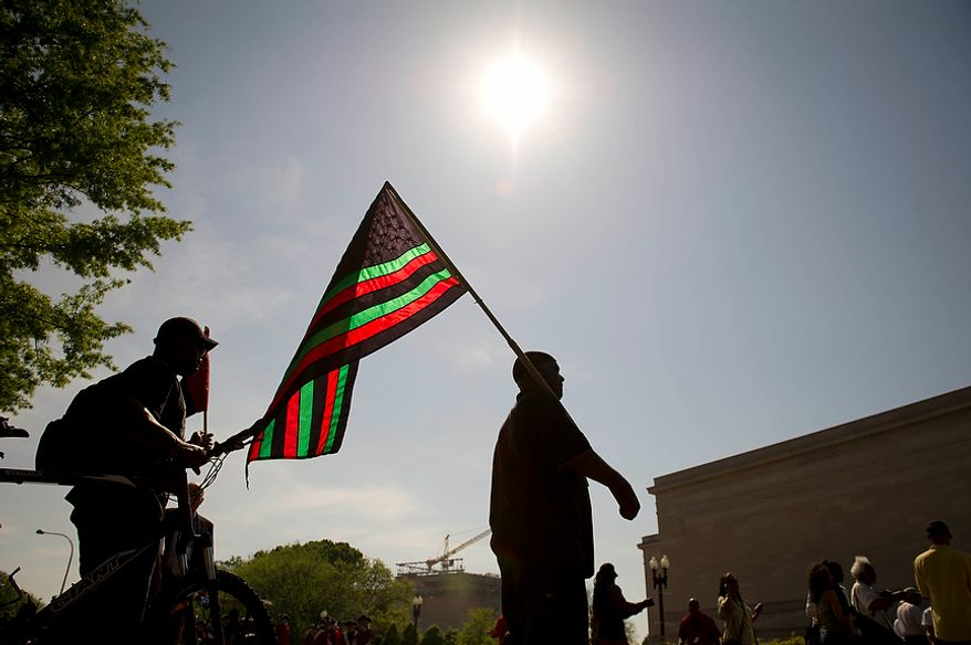 A man who did not want to be identified holds a flag prior to marching in the District of Columbia Emancipation Day 2012 parade in Washington, D.C., Monday, April 16, 2012., celebrating the150th anniversary of the District of Columbia Emancipation Act. 150 ears ago, on April 16, 1862, President Abraham Lincoln signed a bill ending slavery in the District of Columbia. Passage of this law came 8 1/2 months before President Lincoln signed his Emancipation Proclamation. (Rod Lamkey Jr/The Washington Times)