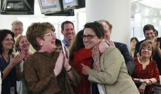 Associated Press executive editor Kathleen Carroll (left) applauds April 16, 2012, as AP reporter Adam Goldman (center) is hugged after winning the Pulitzer Prize for Investigative Reporting with three colleagues in New York. They revealed a secret New York Police Department program that spied on Muslim neighborhoods. (Associated Press)