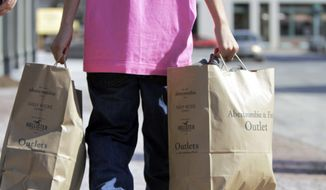 **FILE** A shopper carries bags of merchandise in Freeport, Maine, on March 12, 2012. (Associated Press)
