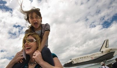 Kyra DeStefano, 7, of Ashburn, Va., and her mother, Secili De Stefano, are overjoyed to be at Washington Dulles International Airport for the flyover and landing of Space Shuttle Discovery on Tuesday. (Andrew Harnik/The Washington Times)