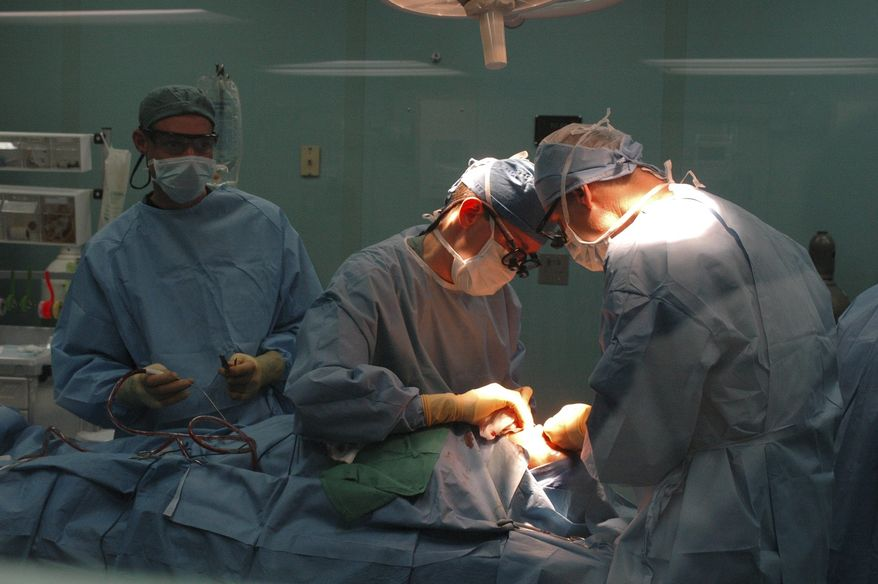 **FILE** Air Force Maj. Richard Buck, Navy Lt. Cmdr. Graig Salt and Navy Capt. Craig Cupp work June 9, 2006, to reconstruct the cleft lip of a 13-year-old girl aboard the U.S. Navy hospital ship USNS Mercy in Jolo, Philippines. (Courtesy of U.S. Navy)