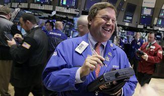 Trader Stephen Mara (center) works April 17, 2012, on the floor of the New York Stock Exchange. (Associated Press)