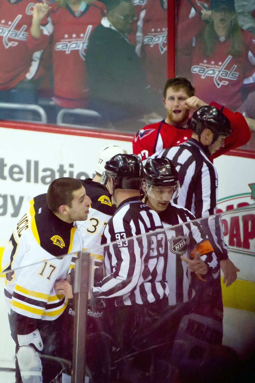 Washington Capitals defenseman Karl Alzner (27), top right, taunts Boston Bruins left wing Milan Lucic (17) during a scuffle in the third period as the Washington Capitals lose to the Boston Bruins in Game 3 of their first-round series, 4-3, at Verizon Center in Washington, D.C., on Monday, April 16, 2012. (Andrew Harnik/The Washington Times)