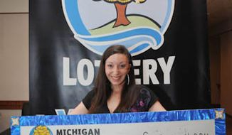 Amanda Clayton holds her $1 million lottery check on Thursday, March 8, 2012. (AP Photo/Courtesy of the Michigan Lottery via Detroit Free Press)