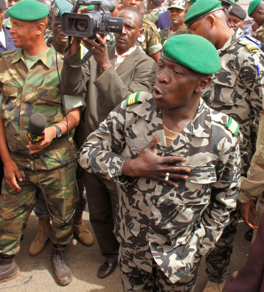 **FILE** Coup leader Capt. Amadou Haya Sanogo (right) speaks March 29, 2012, during a walkabout at the airport in Bamako, Mali. (Associated Press)