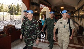 U.N. observers, led by Moroccan Col. Ahmed Himmiche (left), leave the Sheraton Hotel in Damascus, Syria, on Monday, April 16, 2012. (AP Photo/Bassem Tellawi)