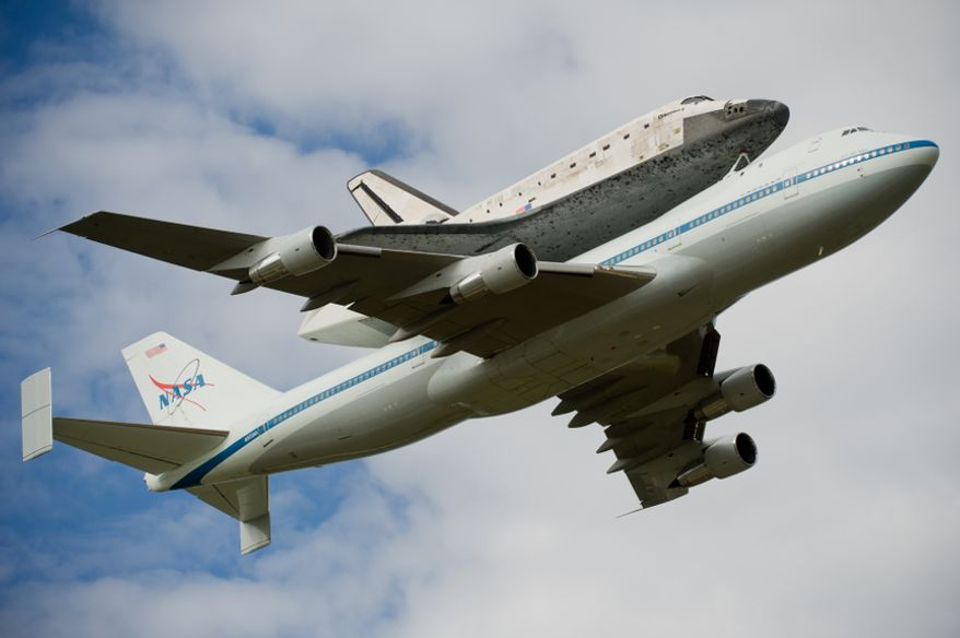 The space shuttle Discovery does a flyby before arriving by 747 carrier aircraft at Washington Dulles International Airport, Chantilly, Va., Tuesday, April 17, 2012. After completing 39 missions and spending 365 days in space, the historic spacecraft will make its final destination at the Steven F. Udvar-Hazy Center, a Smithsonian museum, located in Chantilly, Va., on Thursday, April 19. (Andrew Harnik/The Washington Times)