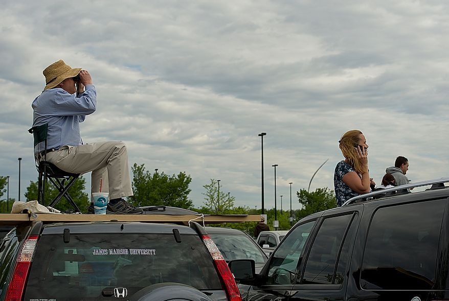 Dennis Smyers, left, of Reston, Va., sits on IKEA shelves on top of his car to get a better view of the space shuttle Discovery as it flies past the Smithsonian Air and Space Museum's Udvar-Hazy Center in Chantilly, Va., on Tuesday, April 17, 2012. At right, Cheryl Baker of Centreville, Va., peeks her head out of her sunroof to get a view too. (Barbara L. Salisbury/The Washington Times)