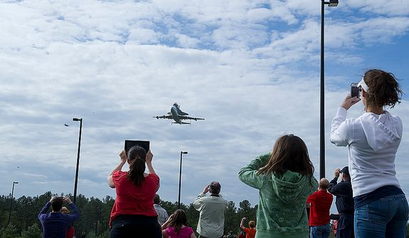 People photograph the space shuttle Discovery as it flies piggyback on a 747 past the Smithsonian Air and Space Museum Udvar-Hazy Center in Chantilly, Va., on Tuesday, April 17, 2012. The shuttle left the Kennedy Space Center Tuesday morning and flew around Washington, D.C. before finally landing at Washington Dulles International Airport. Discovery will now be towed over to the Udvar-Hazy center, where it will take the place of the Enterprise in a welcoming ceremony on Thursday. (Barbara L. Salisbury/The Washington Times)