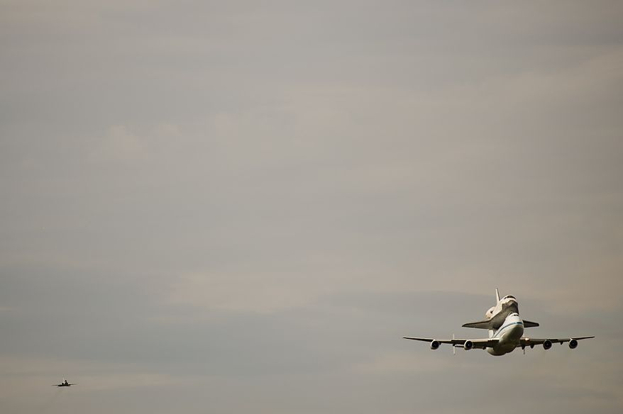 The Space shuttle Discovery does a flyby before arriving by 747 carrier aircraft at Washington Dulles International Airport, Chantilly, Va., Tuesday, April 17, 2012. After completing 39 missions and spending 365 days in space, the historic spacecraft will make its final destination at the Steven F. Udvar-Hazy Center, a Smithsonian museum, located in Chantilly, Va. on Thursday, April 19th. (Andrew Harnik/The Washington Times)