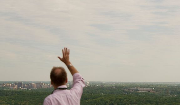 A man waves as he joins others standing atop a platform on one of the towers at the Washington National Cathedral, watching as the NASA Space Shuttle Discovery, being carried piggyback on a modified Boeing 747, makes it's way in the skies above Washington, D.C., Tuesday, April 17, 2012, as it makes it's way to the Steven F. Udvar-Hazy Center in Chantilly, Va. (Rod Lamkey Jr/The Washington Times)