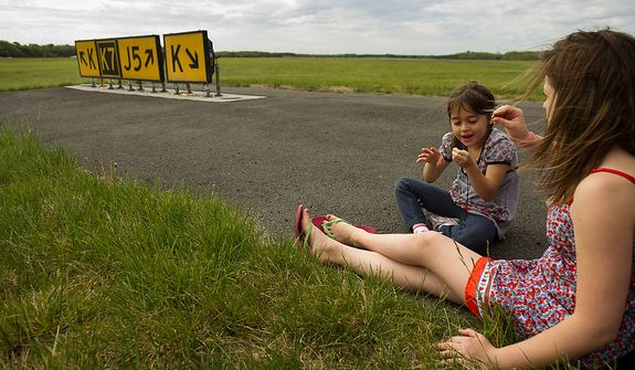 Kyra DeStefano, 7, of Ashburn, Va., left, and Molly Manning, 13, of South Riding, Va., right, wait next to the runway before the space shuttle Discovery arrives by 747 carrier aircraft at Washington Dulles International Airport, Chantilly, Va., Tuesday, April 17, 2012. After completing 39 missions and spending 365 days in space, the historic spacecraft will make its final destination at the Steven F. Udvar-Hazy Center, a Smithsonian museum, located in Chantilly, Va. on Thursday, April 19th. (Andrew Harnik/The Washington Times)