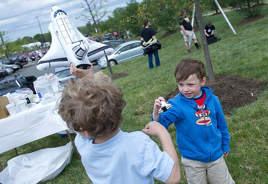 Drew Schwartzman, left, 5, of Baltimore, Md., and Alexander Leigh, 3, of Round Hill, Va., play with toy shuttles outside the Smithsonian Air and Space Museum's Udvar-Hazy Center in Chantilly, Va., on Tuesday, April 17, 2012 as they wait for the space shuttle Discovery to fly by on its way to Washington Dulles International Airport. (Barbara L. Salisbury/The Washington Times)