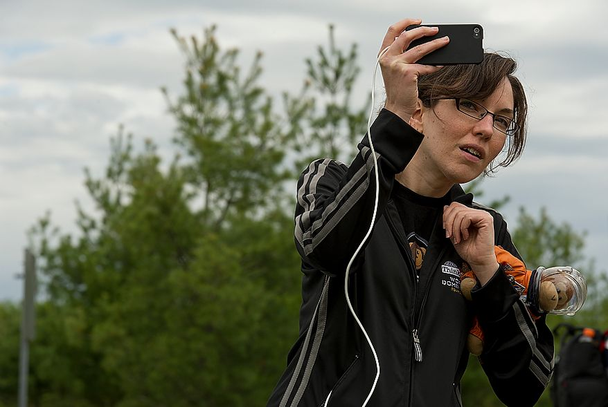 """Carrie Gouldin of Washington, D.C. with Think Geek holds """"Timmy"""" the monkey as she takes video of the space shuttle Discovery flying past the Smithsonian Air and Space Museum's Udvar-Hazy Center in Chantilly, Va., on Tuesday, April 17, 2012. Timmy has been to at least five shuttle launches. (Barbara L. Salisbury/The Washington Times)"""