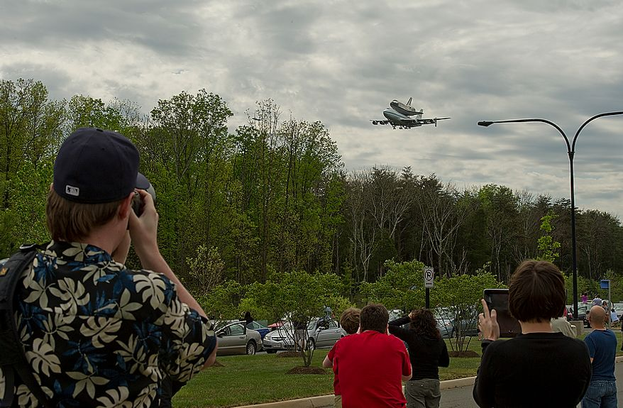 People photograph the Discovery as it flies past the Smithsonian Air and Space Museum Udvar-Hazy Center in Chantilly, Va., on Tuesday, April 17, 2012. The shuttle left the Kennedy Space Center Tuesday morning and flew around Washington, D.C. before finally landing at Washington Dulles International Airport. Discovery will now be towed over to the Udvar-Hazy center, where it will take the place of the Enterprise in a welcoming ceremony on Thursday. (Barbara L. Salisbury/The Washington Times)