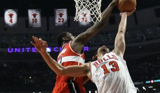 Washington Wizards forward Kevin Seraphin (13) blocks the shot of Chicago Bulls center Joakim Noah, during the first half of an NBA game Monday, April 16, 2012, in Chicago. (AP Photo/Charles Rex Arbogast)