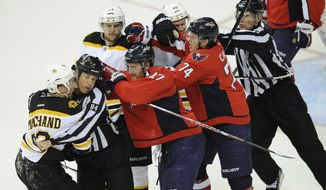 Boston Bruins left wing Brad Marchand, left, Dennis Seidenberg (44) and David Krejci (46) scuffle with Washington Capitals defenseman Karl Alzner (27) and John Carlson (74) during the third period of Game 3 of the first-round playoff series, Monday, April 16, 2012, in Washington. The Bruins won 4-3. (AP Photo/Nick Wass)