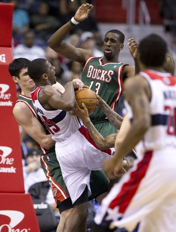 Washington Wizards' Jordan Crawford (15) is crowded by Milwaukee Bucks' Ersan Ilyasova (7), Ekpe Udoh (13) and Monta Ellis (obscured) during the first half of an NBA basketball game in Washington, Wednesday, April 18, 2012. (AP Photo/Manuel Balce Ceneta)
