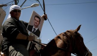 Druze man rides a horse while holding a knife and a photograph of Syrian President Bashar Assad on April 17, 2012, during Syria's Independence Day in the village of Majdal Shams in the Golan Heights, near the border with Syria and Israel. (Associated Press)