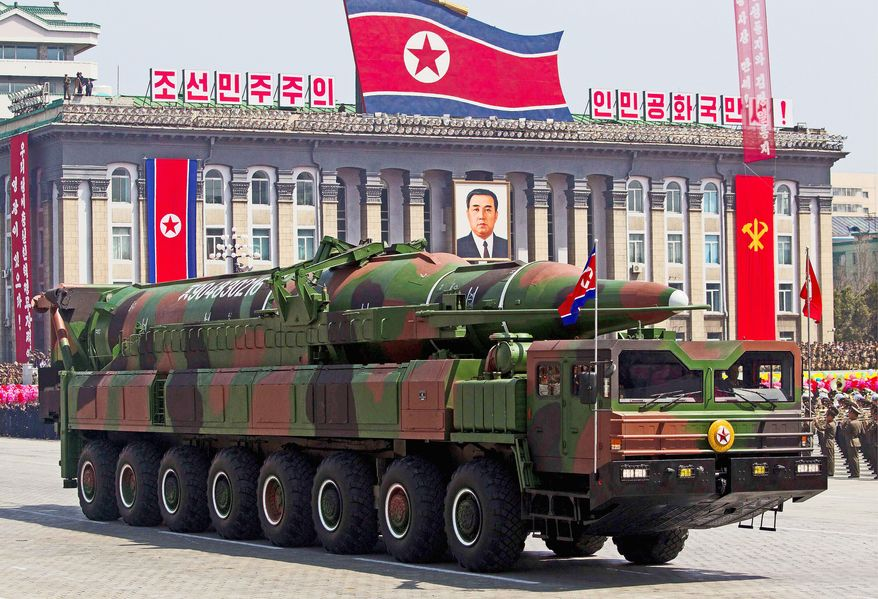 """Vehicles transporting North Korean missiles on display over the weekend were made or designed by China, analysts say. Meanwhile, a propaganda billboard in Pyongyang translates as """"Let's raise the spirits of winners and build a strong and prosperous nation!"""" North Korea has yet to launch a multistage missile successfully. (Associated Press)"""