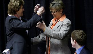 Former Tennessee women's basketball coach Pat Summitt (left) gives her whistle to new coach Holly Warlick at her farewell news conference. Warlick played under Summitt and was a Lady Vols assistant for 27 seasons. (Associated Press)