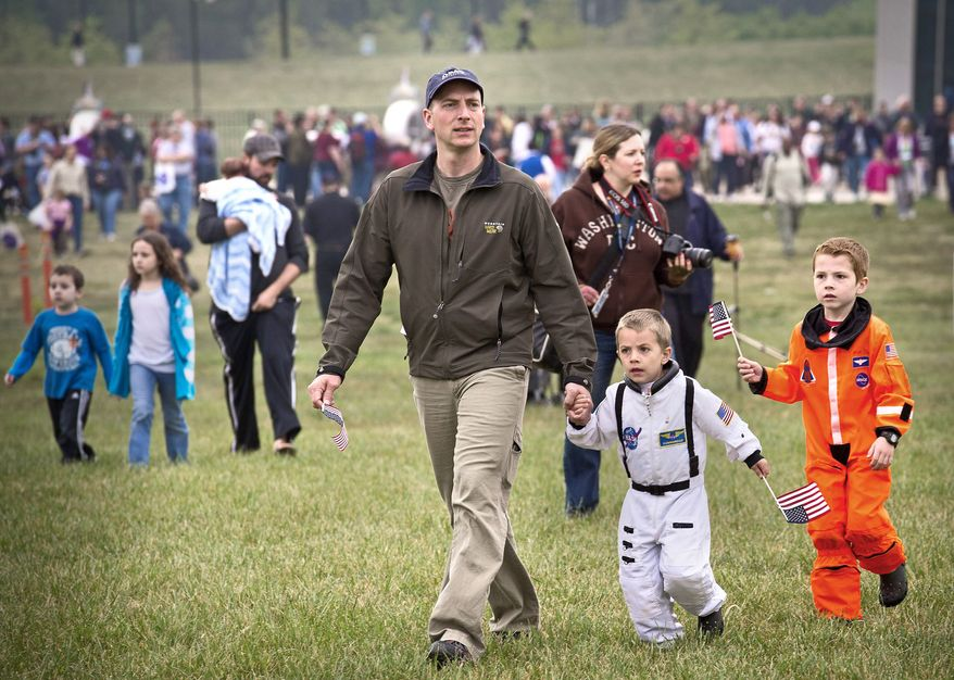 Chester Hull of Charlottesville (above) and his two sons, Bryant, 4, (center) and Cooper, 6, make their way to the ceremonial arrival of Discovery. (Rod Lamkey Jr./The Washington Times)