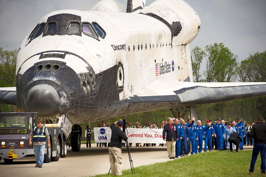 Discovery is towed into place behind the stage to be used as a backdrop during the celebration of its arrival at the Steven F. Udvar-Hazy Center in Chantilly on Thursday. (Rod Lamkey Jr./The Washington Times)
