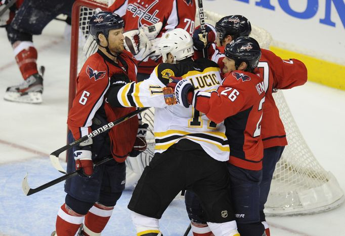 Washington Capitals defenseman Dennis Wideman and Matt Hendricks scuffle with Boston Bruins left wing Milan Lucic during the third period of Game 3 of the first-round playoff series, Monday, April 16, 2012, in Washington. (AP Photo/Nick Wass)