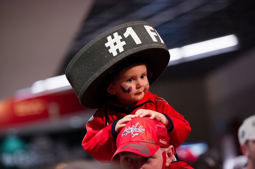 Aiden Witmer, 2, of Alexandria, Va. sits on the shoulders of his dad, Josh, on the way to their seats before the Washington Capitals take on the Boston Bruins in game four of National Hockey League first round playoff hockey at the Verizon Center, Washington, D.C., Thursday, April 19, 2012. (Andrew Harnik/The Washington Times)