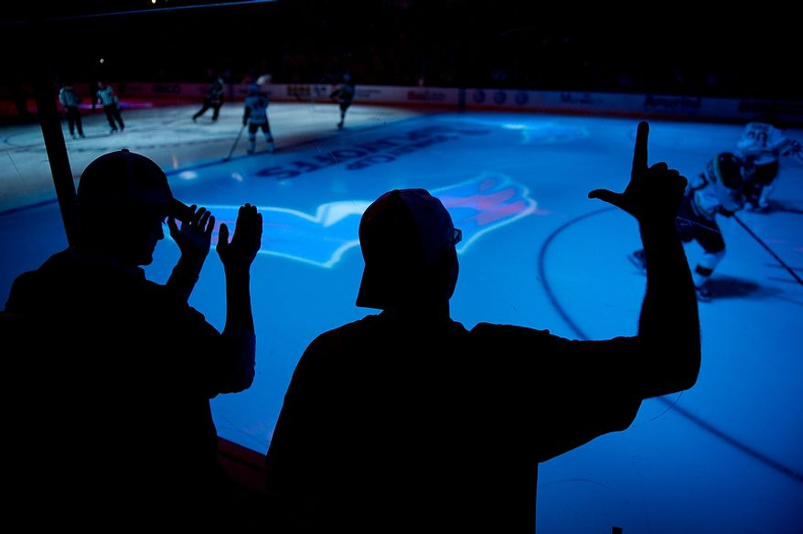 """Jason Bach, right, of Crownsville, Md., right, makes an """"L"""" for """"Loser"""" as the Boston Bruins skate out to the ice before the puck drop as the Washington Capitals take on the Boston Bruins in game four of National Hockey League first round playoff hockey at the Verizon Center, Washington, D.C., Thursday, April 19, 2012. (Andrew Harnik/The Washington Times)"""