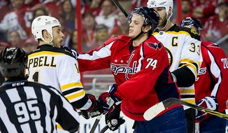 Boston Bruins center Gregory Campbell (11), left, and Washington Capitals defenseman John Carlson (74) get physical after a play in the first period as the Washington Capitals take on the Boston Bruins in game four of National Hockey League first round playoff hockey at the Verizon Center, Washington, D.C., Thursday, April 19, 2012. (Andrew Harnik/The Washington Times)