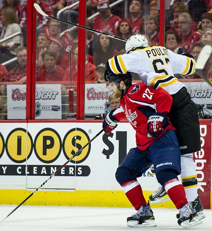 Boston Bruins left wing Benoit Pouliot (67) (right) goes over the head of Washington Capitals defenseman Karl Alzner (27) as they battle for the puck in the first period as the Caps took on the Bruins in game four of the National Hockey League's first-round playoffs at the Verizon Center in Washington on Thursday, April 19, 2012. (Andrew Harnik/The Washington Times)
