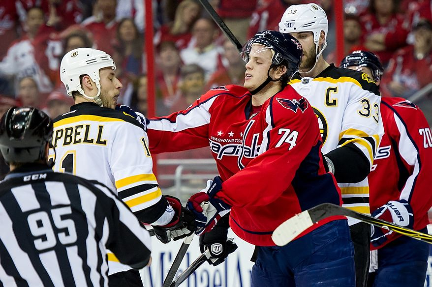 Boston Bruins center Gregory Campbell (11) (left) and Washington Capitals defenseman John Carlson (74) get physical after a play in the first period as the Caps took on the Bruins in game four of the National Hockey League's first-round playoffs at the Verizon Center in Washington on Thursday, April 19, 2012. (Andrew Harnik/The Washington Times)