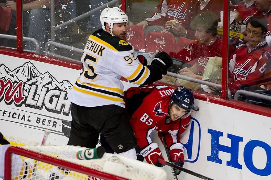 Boston Bruins defenseman Johnny Boychuk (55) and Washington Capitals center Mathieu Perreault (85) slam into the wall in the second period as the Caps took on the Bruins in game four of the National Hockey League's first-round playoffs at the Verizon Center in Washington on Thursday, April 19, 2012. (Andrew Harnik/The Washington Times)