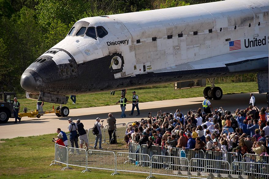 People cheer and greet the NASA space shuttle Discovery as it is brought into the James S. McDonnell Space Hangar at the National Air and Space Museum's Steven F. Udvar-Hazy Center in Chantilly, Va., on Thursday, April 19, 2012. (Rod Lamkey Jr./The Washington Times)