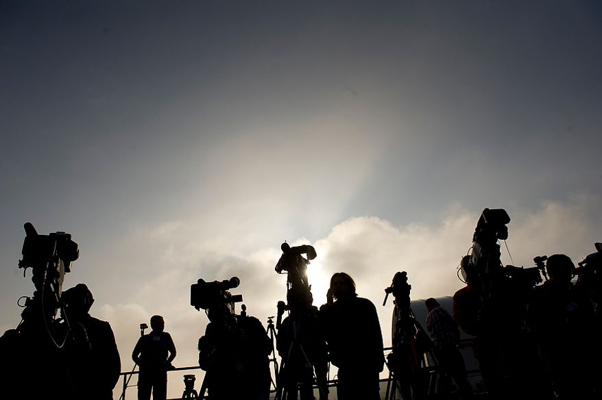News crews set up against a sunrise prior to the ceremonial arrival of the NASA space shuttle Discovery at the National Air and Space Museum's Steven F. Udvar-Hazy Center in Chantilly, Va., on Thursday, April 19, 2012. (Rod Lamkey Jr./The Washington Times)