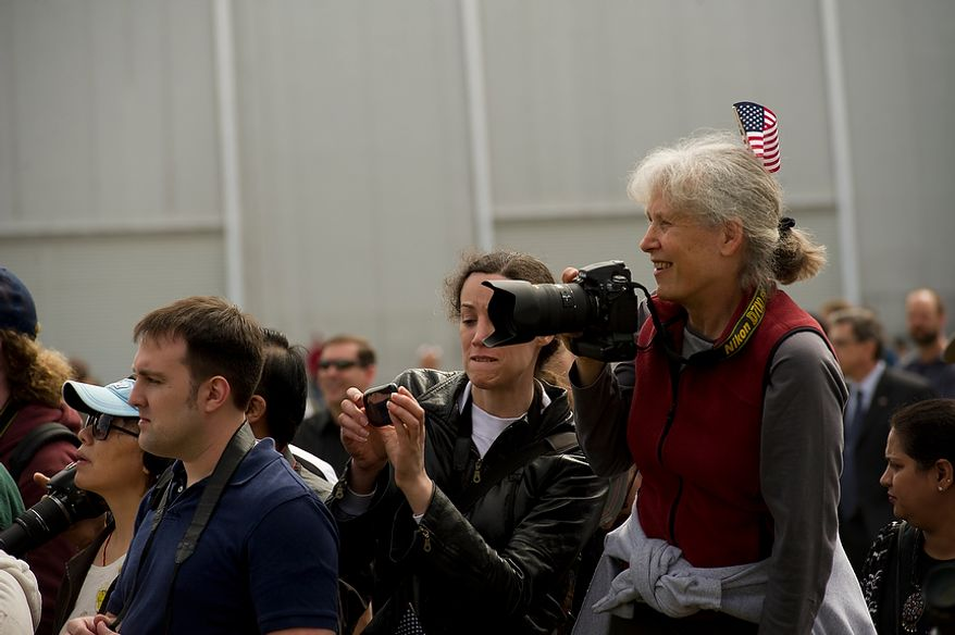 Finding any way they can, people in the crowd try to make photos during the ceremonial arrival of the NASA space shuttle Discovery at the National Air and Space Museum's Steven F. Udvar-Hazy Center in Chantilly, Va., on Thursday, April 19, 2012. (Rod Lamkey Jr./The Washington Times)