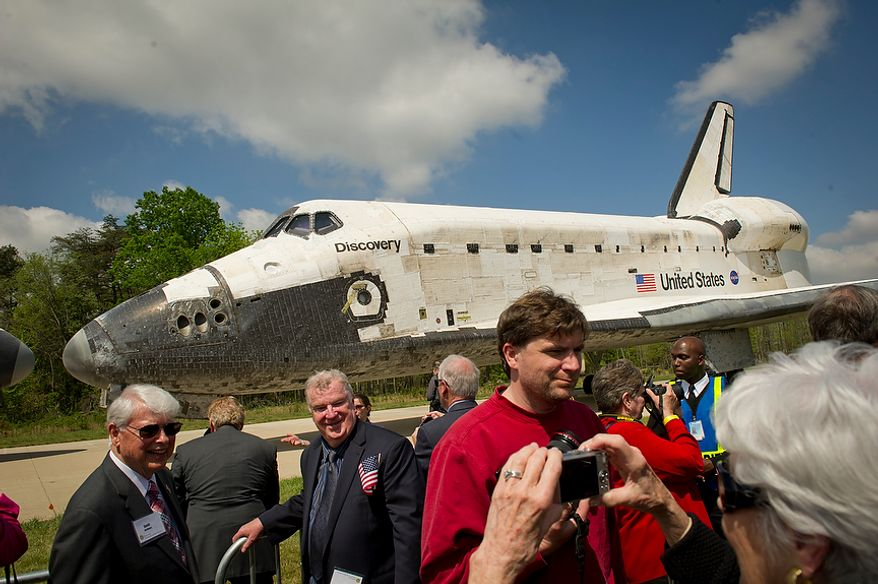 VIPs and others take photos of one another with the NASA space shuttle Discovery during the its ceremonial arrival at the National Air and Space Museum's Steven F. Udvar-Hazy Center in Chantilly, Va., on Thursday, April 19, 2012. (Rod Lamkey Jr./The Washington Times)
