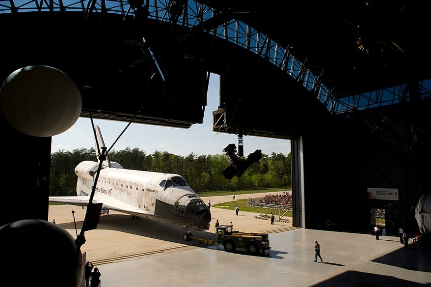 The NASA space shuttle Discovery is brought into the James S. McDonnell Space Hangar at the National Air and Space Museum's Steven F. Udvar-Hazy Center in Chantilly, Va., during its ceremonial arrival on Thursday, April 19, 2012. (Rod Lamkey Jr./The Washington Times)