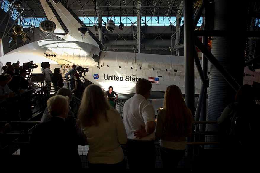 People pack the upper aisles as they watch the NASA space shuttle Discovery as it is parked in the James S. McDonnell Space Hangar at the National Air and Space Museum's Steven F. Udvar-Hazy Center in Chantilly, Va., during its ceremonial arrival on Thursday, April 19, 2012. (Rod Lamkey Jr./The Washington Times)