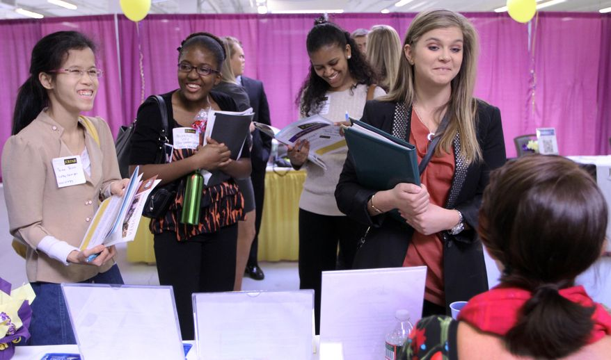 **FILE** Martina Ryberg (right) of Plymouth State University talks April 4, 2012, with Tara Rossetti of On Call International during a job fair for college students in Manchester, N.H. (Associated Press)