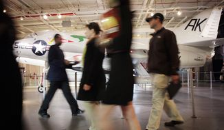 ** FILE ** People pass a military jet while attending a job fair for veterans on March 28, 2012, at the Intrepid Sea, Air and Space Museum in New York. (Associated Press)