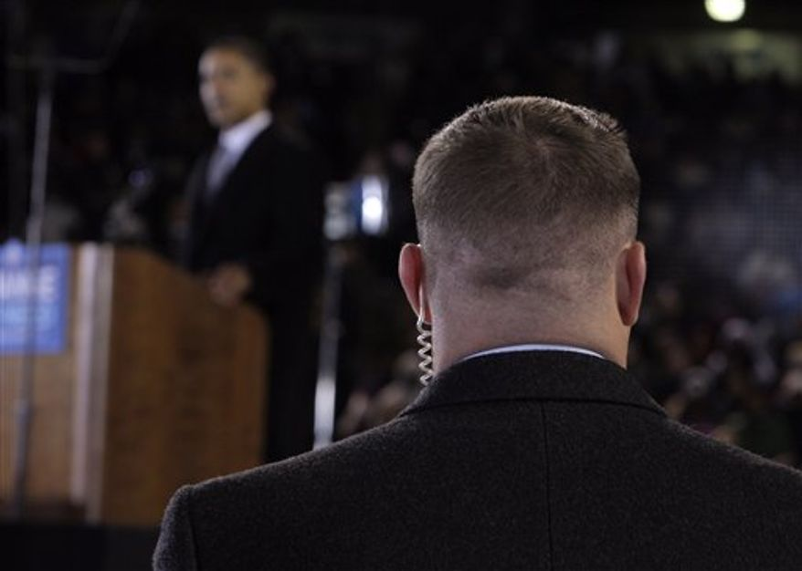 "FILE - In this Oct. 28, 2008 file photo, a Secret Service agent stands near then presidential candidate Barack Obama, background, at a rally in Norfolk, Va. Moving swiftly, the Secret Service forced out three agents Wednesday, April 18, 2012 in a prostitution scandal that has embarrassed President Obama. A senior congressman welcomed the move to hold people responsible for the tawdry episode but warned ""it's not over."" (AP Photo/Jae C. Hong, File)"