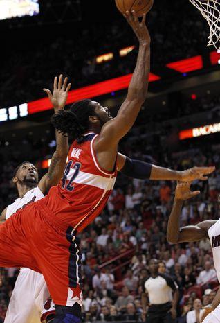 Washington Wizards' Nene scores the the game-winning basket against the Miami Heat in Miami on Saturday, April 21, 2012. (AP Photo/Alan Diaz)