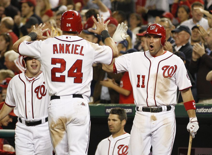 Washington Nationals Ryan Zimmerman congratulates teammate Rick Ankiel who scored a run during the eighth inning of against the Miami Marlins on Friday, April 20, 2012, in Washington. The Nationals defeated the Marlins 2-0. (AP Photo/Evan Vucci)