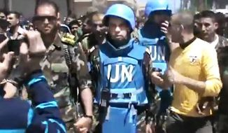 This image made from amateur video purports to show a Free Syrian Army solider accompanying U.N. observers in Rastan town in Homs, Syria. (Associated Press)