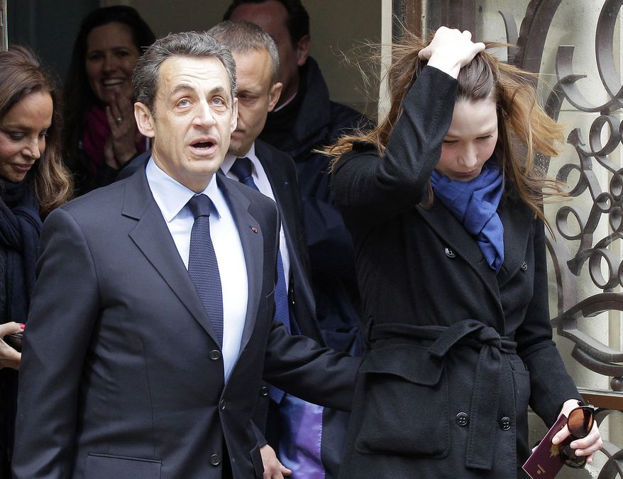 French President Nicolas Sarkozy, who is running for re-election, and his wife, Carla Bruni-Sarkozy, leave after casting their votes in the first round of French presidential balloting in Paris on Sunday, April 22, 2012. (AP Photo/Michel Euler)