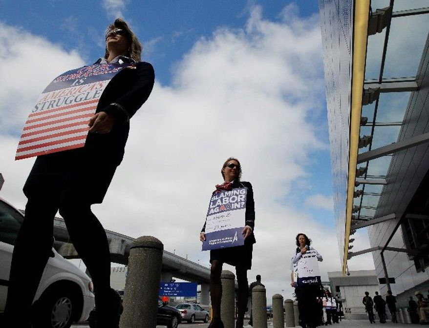 American Airlines flight attendants protest at San Francisco International Airport on Monday. The airline wants to eliminate 13,000 union jobs, freeze or terminate pension plans, curb health benefits, reduce time off, and impose many other cuts. American lost more than $10 billion in the decade leading up to its declaration of bankruptcy in November. (Associated Press)