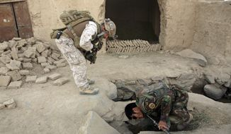 **FILE** A member of U.S. special operations forces and an Afghan National Army soldier search Oct. 31, 2009, for roadside bombs during a joint patrol in Shewan, a former Taliban stronghold in Afghanistan's Farah province. (Associated Press)