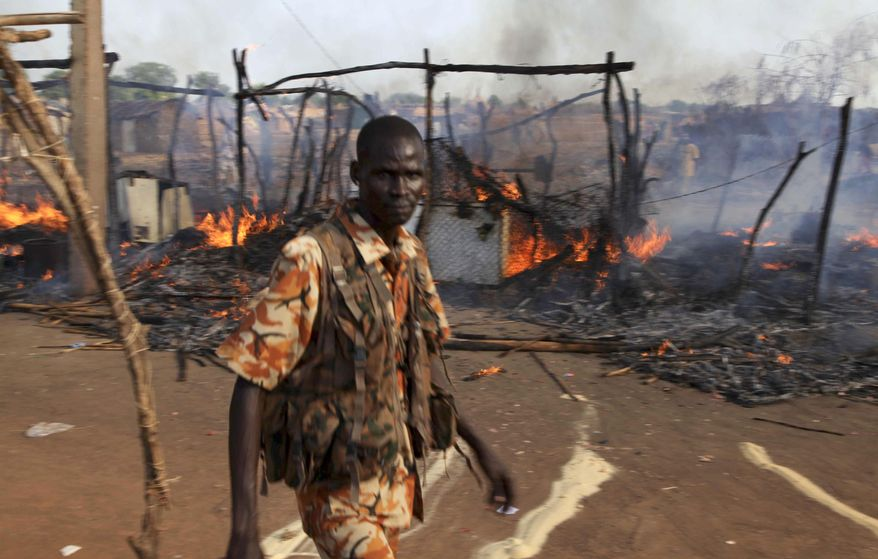 A policeman walks past the smouldering remains of a market in Rubkona, near Bentiu in South Sudan, on April 23, 2012. A boy was killed and at least two people were wounded when Sudanese aircraft bombed the area, an official and witness said, increasing the threat of a full-scale war breaking out between the two nations. (Associated Press)